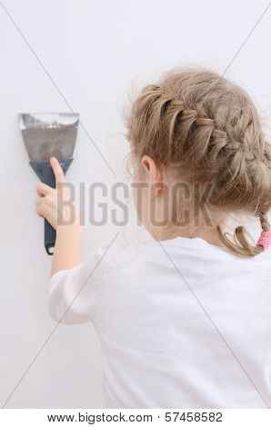 Little Girl Repairs Wall With Spackling Paste.