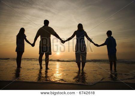 Familie Holding hände auf beobachten den Sonnenuntergang Strand