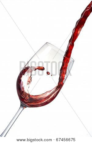 Pouring red wine into a crystal glass creates waves, splash.