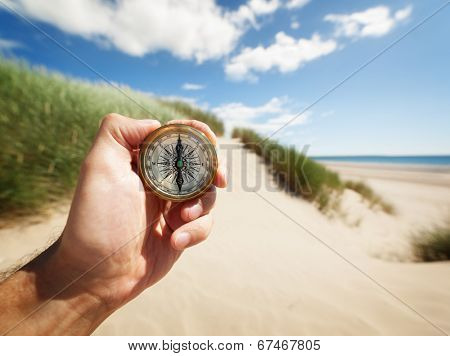Hand holding a compass on the beach by sea concept for guidance, direction, and adventure