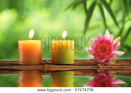 Spa still life with burning candles and water lily.