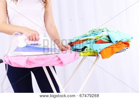 Woman ironing clothes on ironing board, close-up, on light background