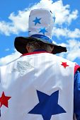 Uncle sam standing tall among the clouds outside. poster