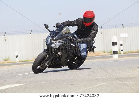 Young Man Wearing Safety Suit And Red Anti Knock Helmet  Riding Big Bike Motorcycle Running In Sharp