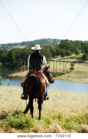 Cowboy riding his horse with lake in the background poster