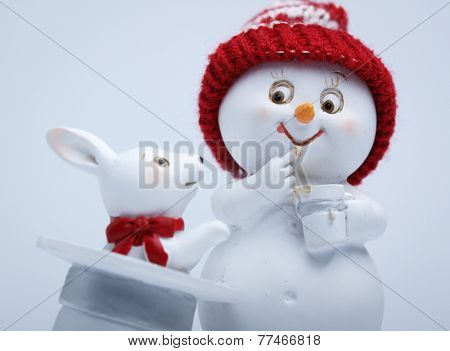 Cheerful snowman and rabbit shows hat trick. The magician conjured a rabbit out of a hat