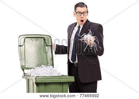Shocked businessman looking into a trash can full of shredded paper isolated on white background