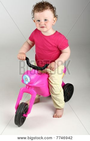 Happy baby girl with her pink bike on grey background