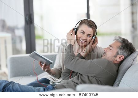 Mature couple at home listening to music with tablet