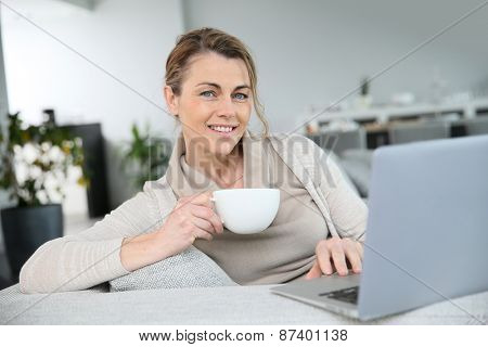 Mature woman relaxing with cup of coffee in front of laptop