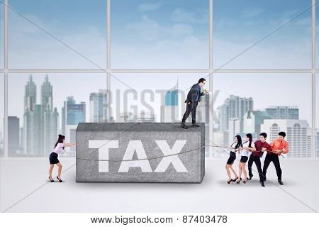 Businesspeople Pulling A Tax Rock
