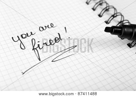 Message You're Fired on notebook with marker, closeup