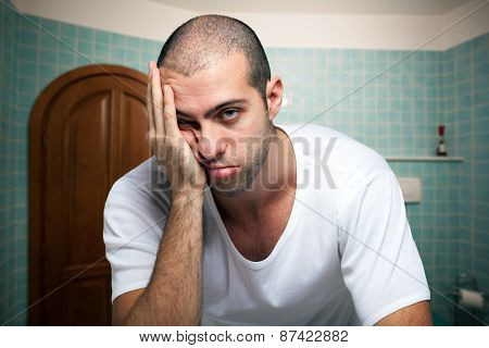 Portrait of a tired man looking in the mirror in the bathroom