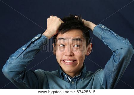 Funny young Asian man making face and looking sideways