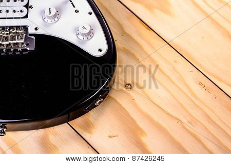 An electric guitar on wooden table.
