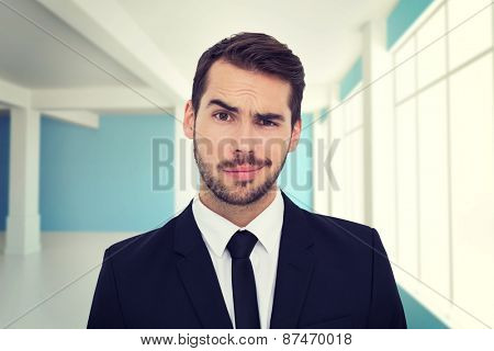 Portrait of a skeptical businessman well dressed against modern blue and white room