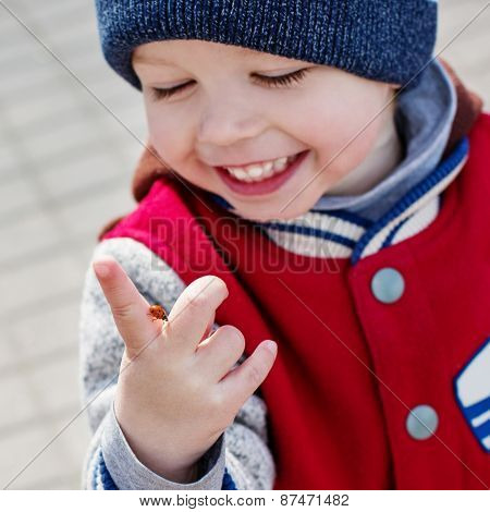 Toddler Smiling Child Looking At A Ladybug