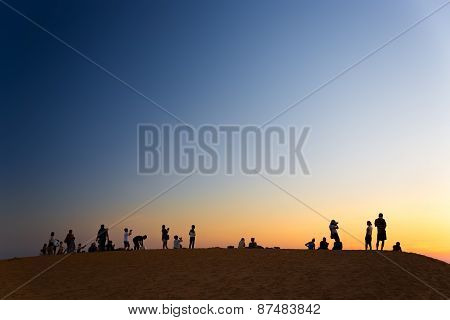 MUI NE, VIETNAM - FEBRUARY 08, 2014: Tourist watching sunset on red sand dunes close to South China