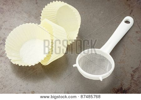 three yellow baking cups and sifter