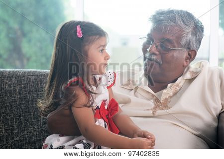 Portrait Indian family at home. Grandparent and grandchild talking together. Asian people living lifestyle. Grandfather and granddaughter.