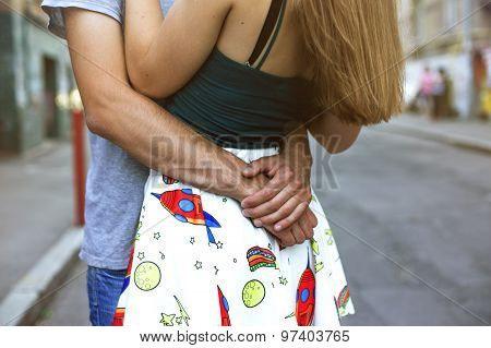 Guy hugs girl, focus on from behind his back in her arms