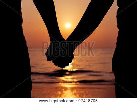 Silhouettes couples holding hands on the beach sunset.