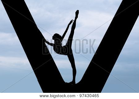 Silhouette of a graceful ballerina in a black bathing suit that makes choreographic exercise in imaginative in support of the bridge against the backdrop of an overcast sky. poster
