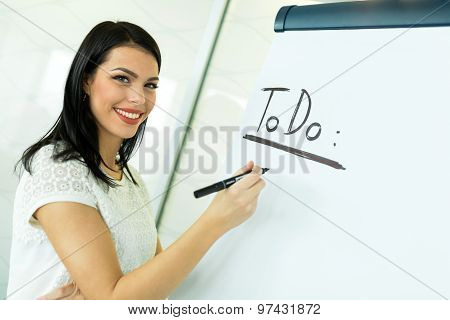Businesswoman Writing Todo Onto A White Writing Board