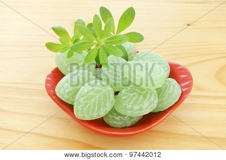 Woodruff leaves and candies in a red porcelain dish on wooden table poster