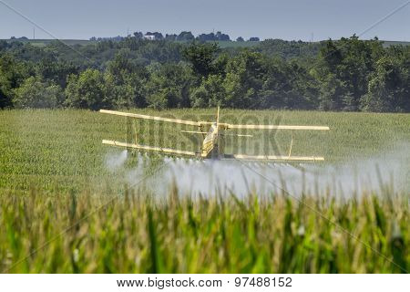 A crop duster applies chemicals to a field of vegetation. poster