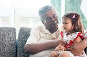 Portrait Indian family at home. Grandparent and grandchild playing together. Asian people living lifestyle. Grandfather and granddaughter. poster