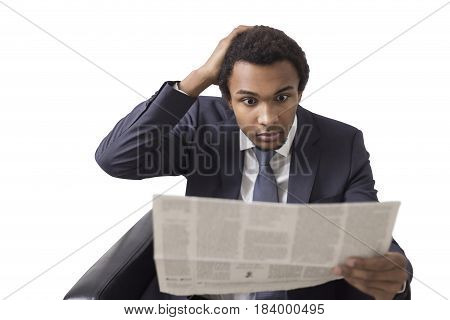 Isolated portrait of a surprised African American businessman sitting in an armchair with a newspaper and looking at it in disbelief