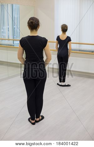 Beautiful woman and girl in black stand near mirror in hall with ballet bar, back view, focus on woman