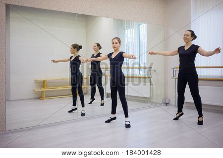 Woman and girl in black do exercises at ballet bar in hall with mirror