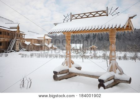 Wooden old-style bench, log buildings in Russian Orthodox Monastery at winter day