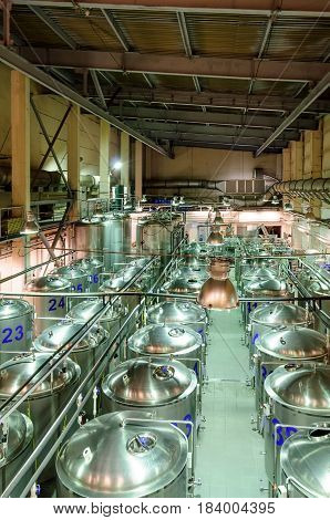 Rows of cisterns from food stainless steel. A small brewery, a shop for beer fermentation.