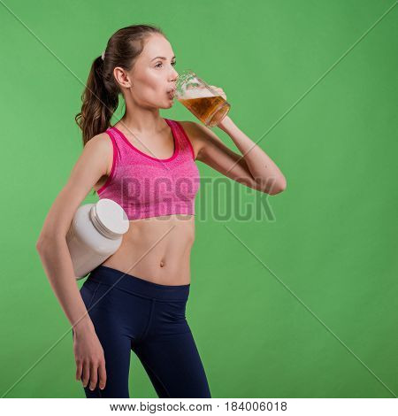 Caucasian girl that chooses between mug of beer or protein shake bottle. Choice concept.