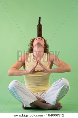 Peaceful young man doing yoga and meditation with bottle of beer on head
