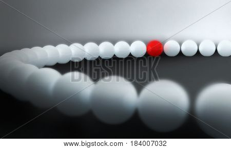 round red ball in a circle of white balls to represent being different