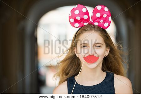 Decorative props on stick. Happy pretty girl or young woman teenager with long blond hair posing with cute mouse ears and paper red lips. Holiday birthday anniversary celebration. Fun party