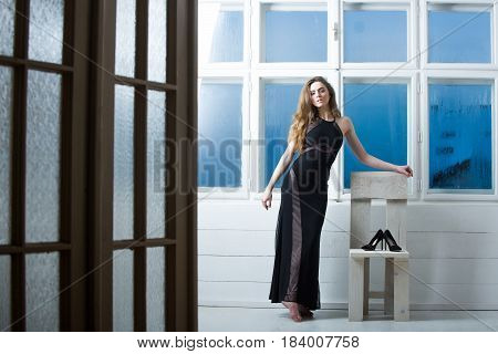Pretty girl or beautiful fashion woman with long blond hair wearing black dress posing with shoes on white wooden chair on misted window background