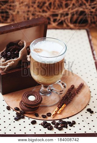 Latte macchiato coffee with cinnamon and cookies