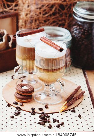 Latte macchiato with cinnamon and cookies on polkadot background