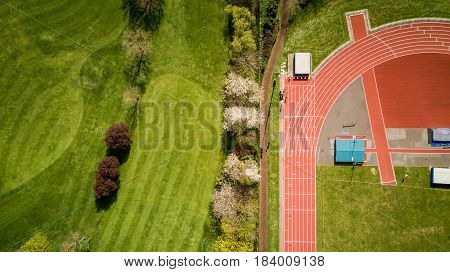 Abstract aerial view looking down onto an athletics running track set against the green of a neighbouring golf course.