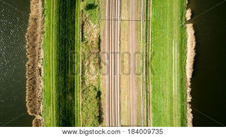 Aerial drone photo of a train track bordered by water and pathways creating abstract mirrored lined textures.