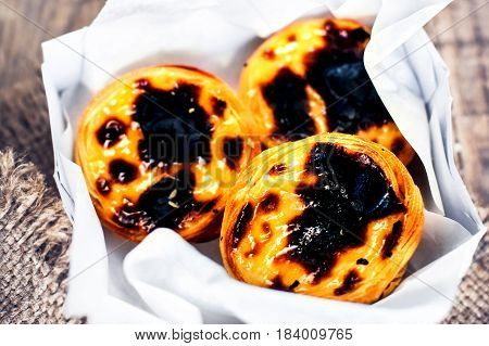 Creamy egg tart with sweet curstard black crust and sugar powder on wooden background. Pasteis de Belem pastry