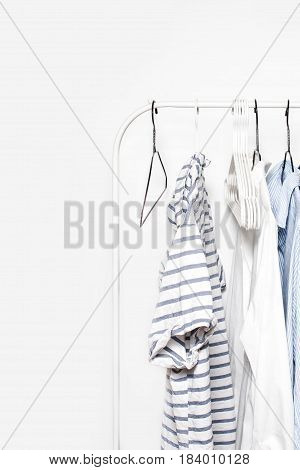 Clothing Rack - Pastel Color Clothes on Cloth Rail over white Wall Background close up with copyspace. Blue White and Stripped t-shirts