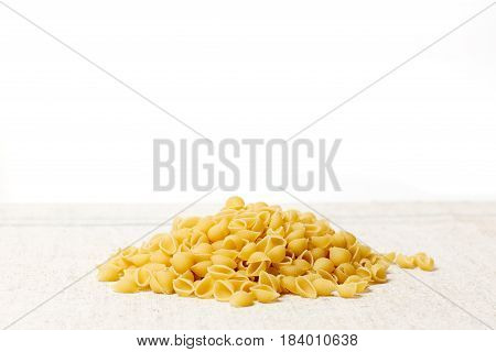 A heap of macaroni on a sacking on a light background. Photo in a rustic style. Top place for design.