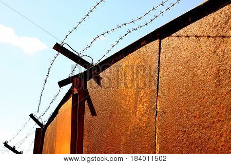 Rusty gates with barbed wire guard the entrance to the prison