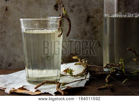 Birch natural juice detox in a glass on a birch bark and with a birch branch. Vintage background. Rusty metal
